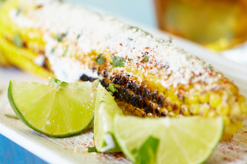 sweet corn on the cob with cheese and lime