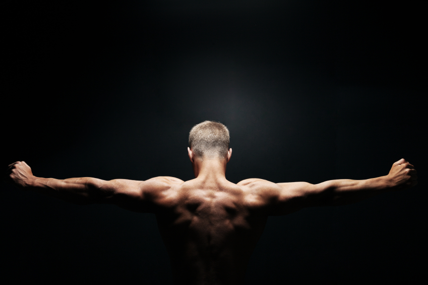 a muscular man flexing his back muscles