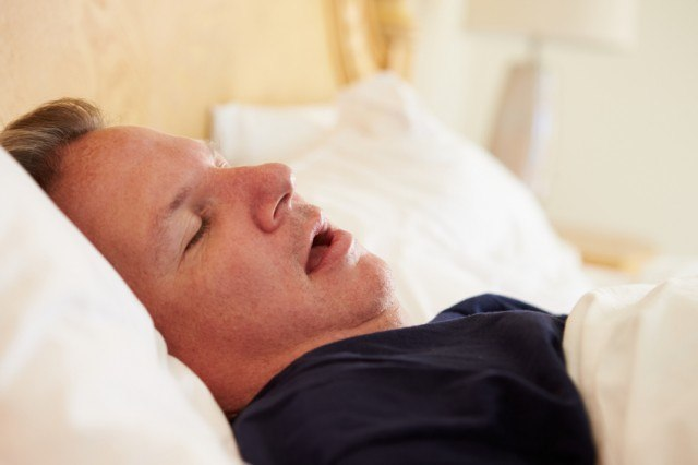 man snoring in bed