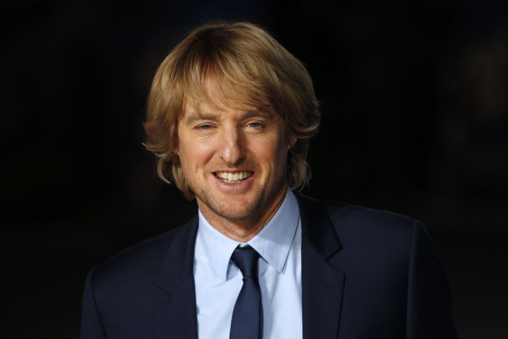Owen Wilson stands in a dark suit