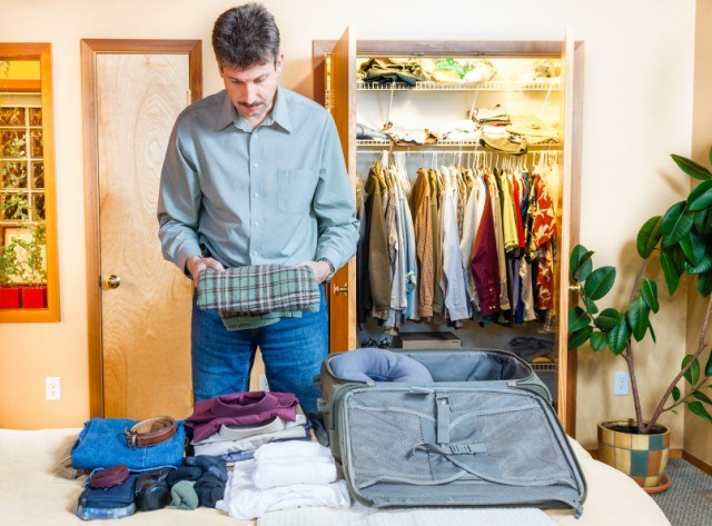 man packing clothes into a suitcase