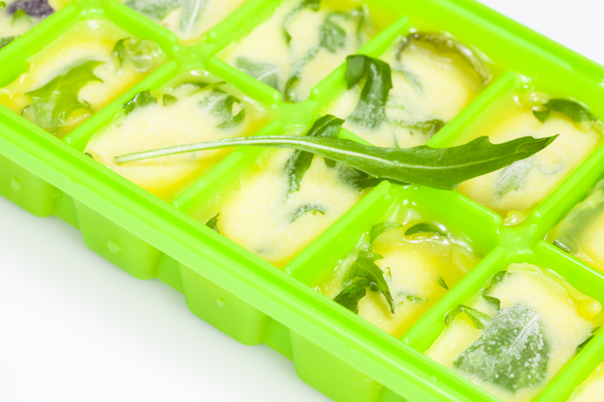 Ice cube tray with herbs and oil
