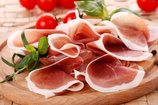Sliced ham on a wooden tray.
