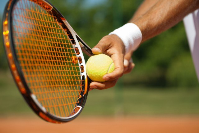 man holding a tennis racket and ball