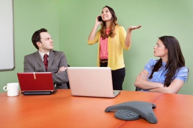 Businesswoman being loud on her phone in front of coworkers