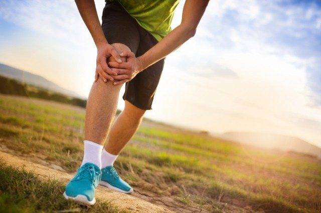 A man grabs his knee while nursing an injury.