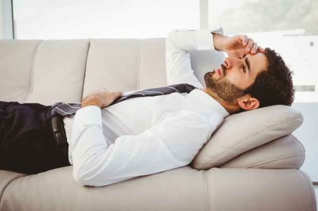 A sick man lays on a couch