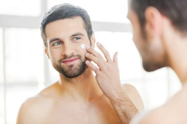 Man putting lotion on his face