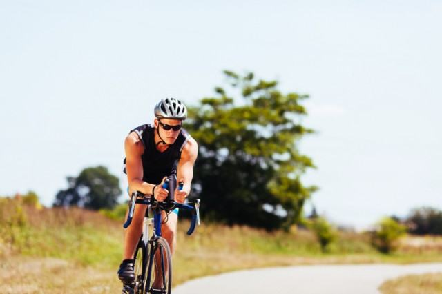 male athlete biking on a road in the country