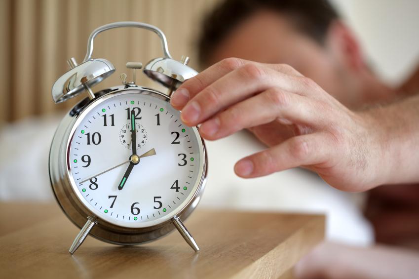 man hitting his alarm clock to sleep in