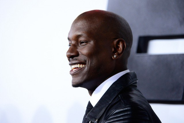 Tyrese Gibson smiles and poses for photos while wearing a black jacket.