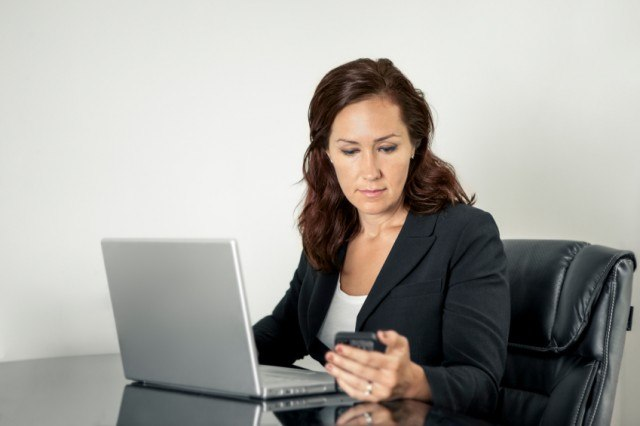 Woman checking her phone in her office