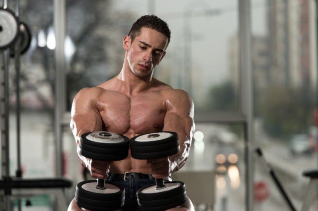 Man focusing while lifting weights