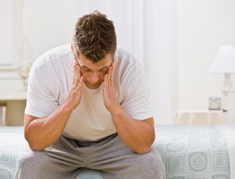 stressed man who is sitting on the bed thinking