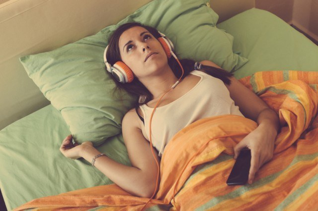 A woman laying in bed listening to music.