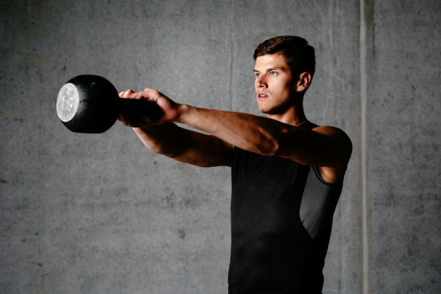 Man using kettlebell while wearing fitness gear.