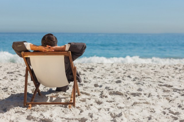 A man sits on a beach chair overlooking the ocean.