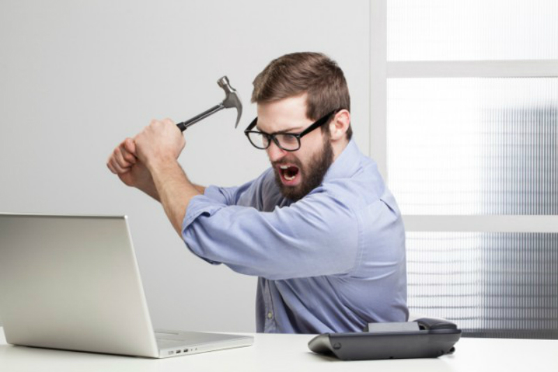 an angry man about to hit his computer with a hammer