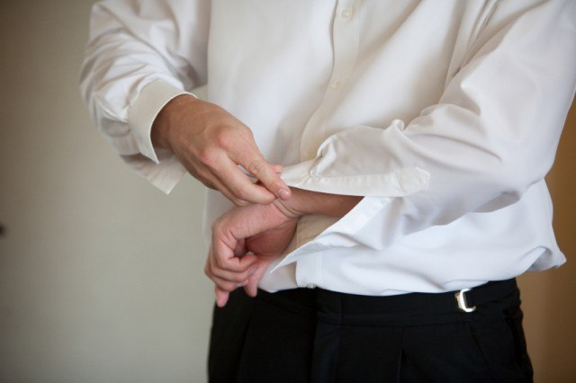 A man putting on his perfect shirt