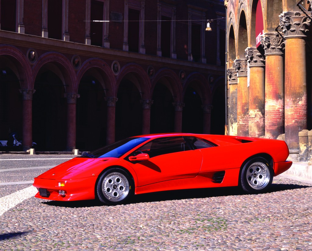 Red 1990 Lamborghini Diablo parked in a town square.