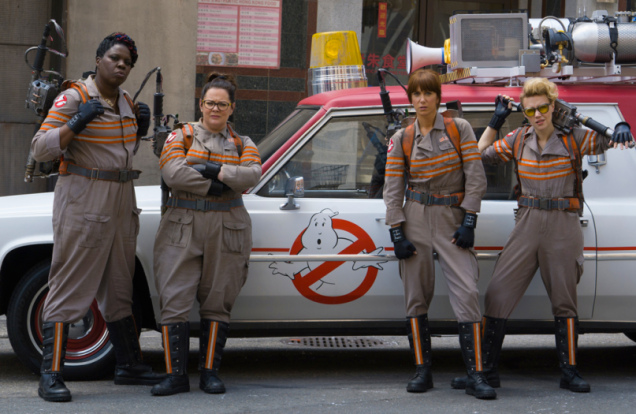 The main cast of the Ghostbusters are standing together in front of their vehicle.