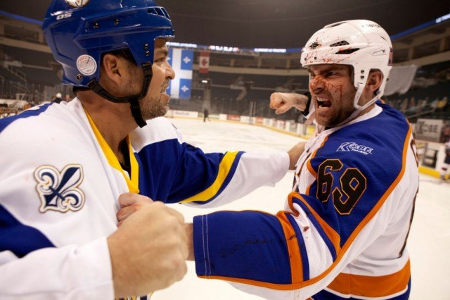 Seann William Scott in a hockey uniform about to punch another player
