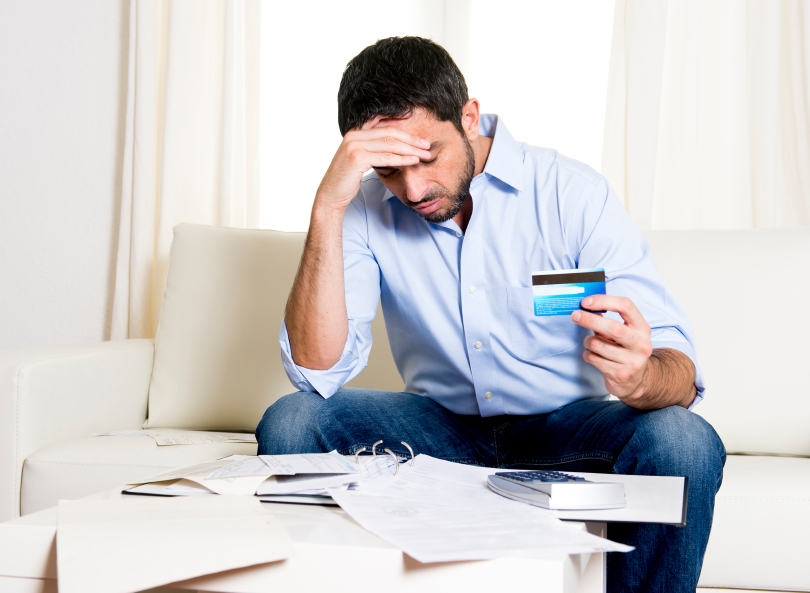 worried man holding credit card