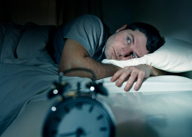 Man with insomnia lies awake at night in his bed