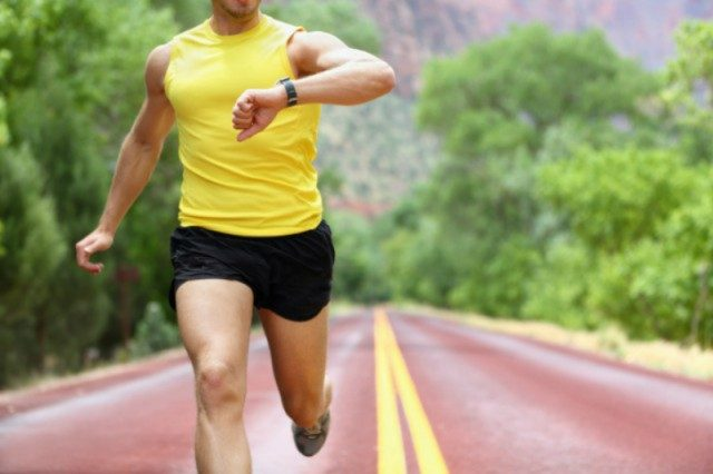 A man in a yellow shirt and black shorts runs on the road while looking at his watch