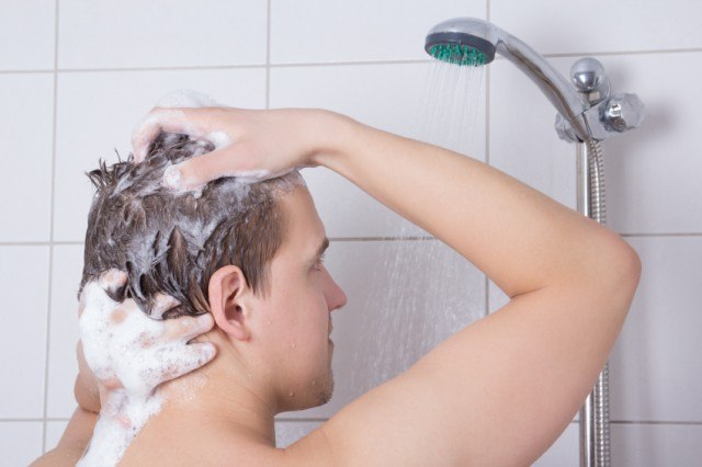 man shampooing his hair in the shower