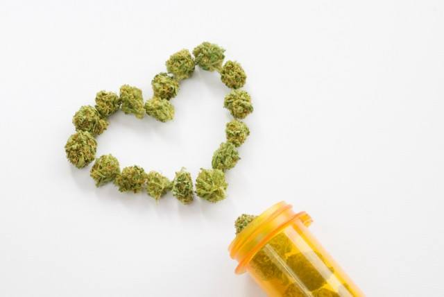 Marijuana laid out to look like a heart and a container on a white table.