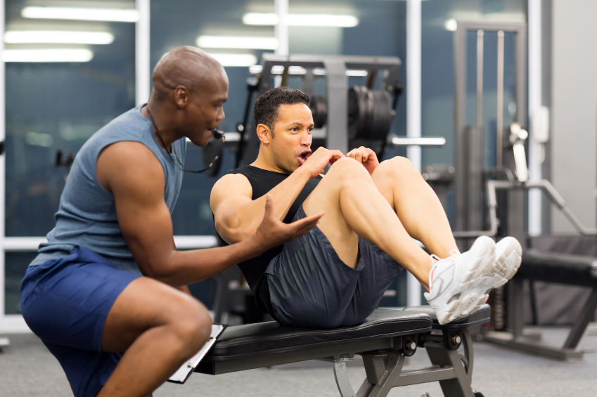 A trainer works with a client in a gym
