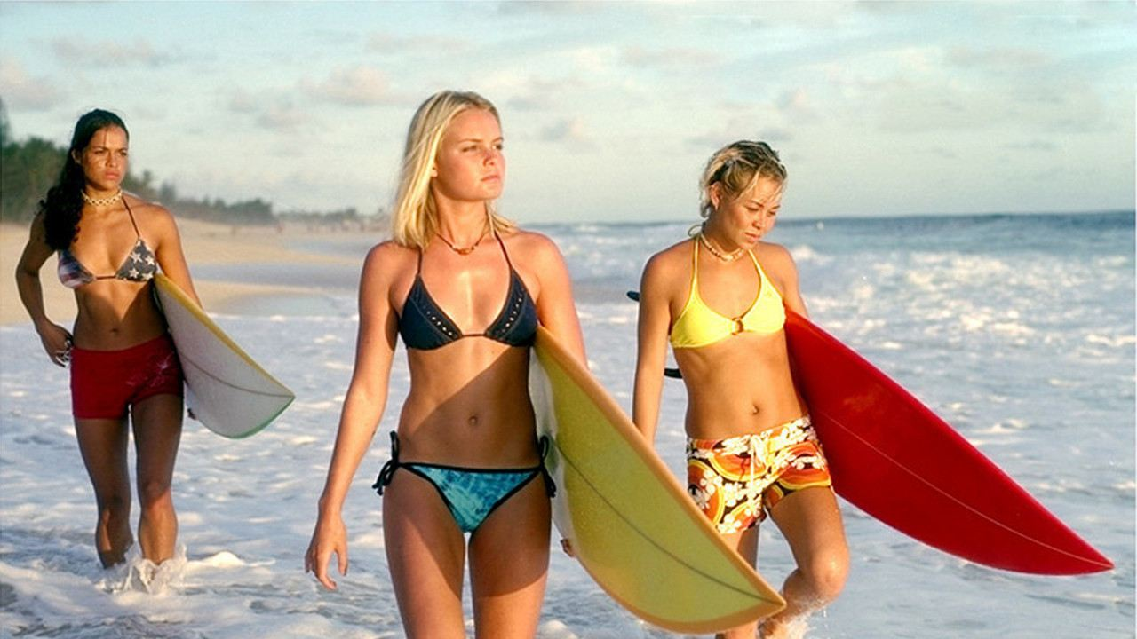 Kate Bosworth walks on the beach holding a surfboard in Blue Crush