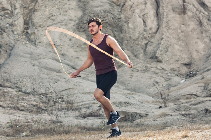 sporty man jumping rope outdoors