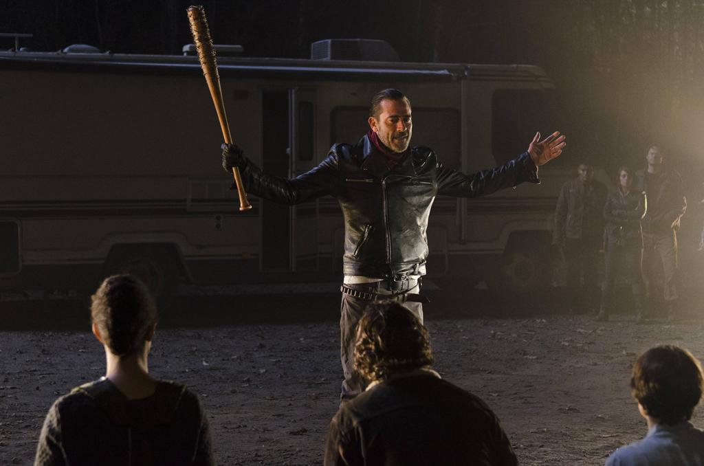 Negan with his arms out, holding his barbed-wire baseball bat in his right hand