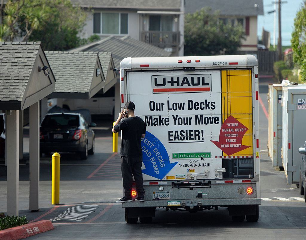 A U-Haul moving truck drives in an apartment complex parking lot.