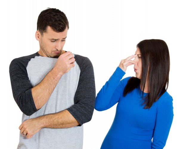 woman holding her nose toward man with bad odor