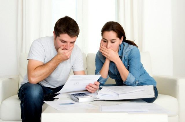 a couple looking at their bills with surprise