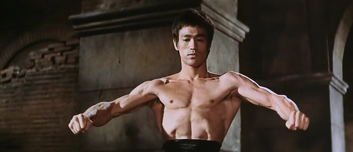 Bruce Lee has his arms out and is flexing.
