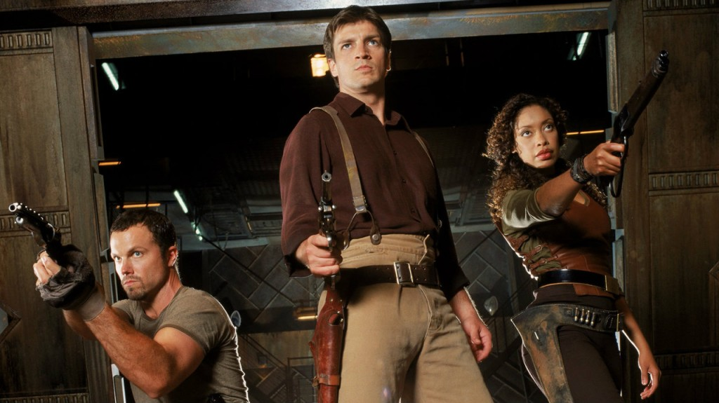 Adam Baldwin, Nathan Fillion and Gina Torres hold guns in a scene from 'Firefly'