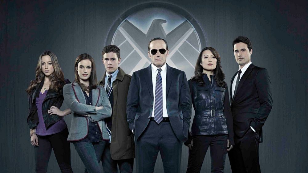 Cast of Agents of SHIELD stand next to one another in front of the SHIELD emblem