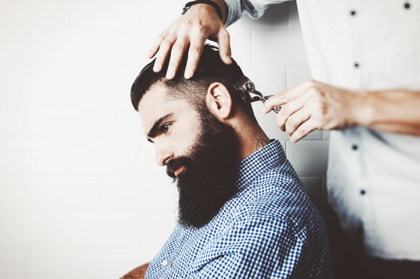 Bearded man getting his hair cut by barber
