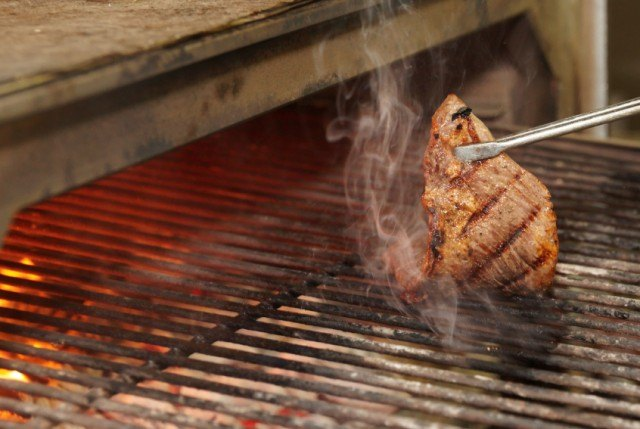 Flipping a steak on the grill   Source: iStock