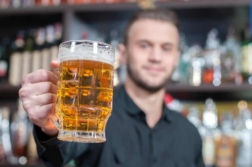 man drinking beer at a bar