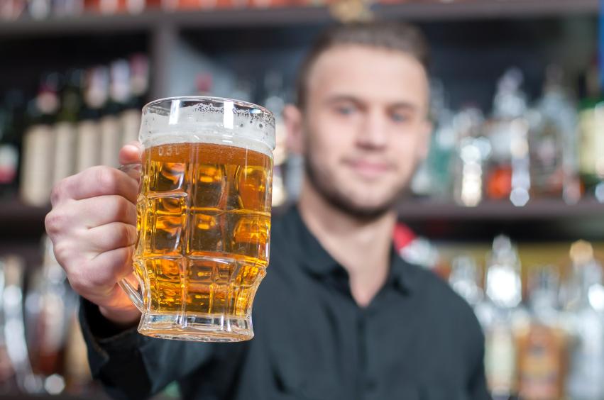 A bartender handing over a mug of cheap beer