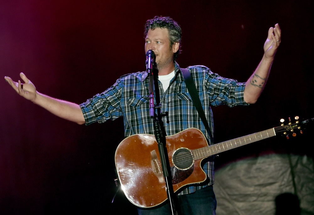 Blake Shelton holds his hands up as he performs on stage.