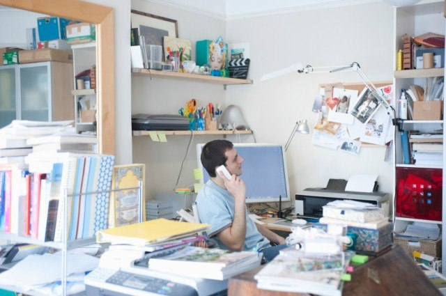 a man working at his messy desk while on the phone