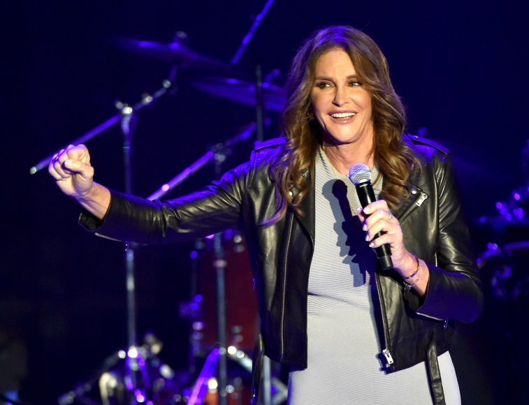 Caitlyn Jenner is smiling and talking on stage with a microphone in one hand and making a fist with the other.