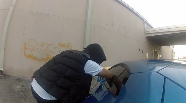 A man is attempting to rob a parked car