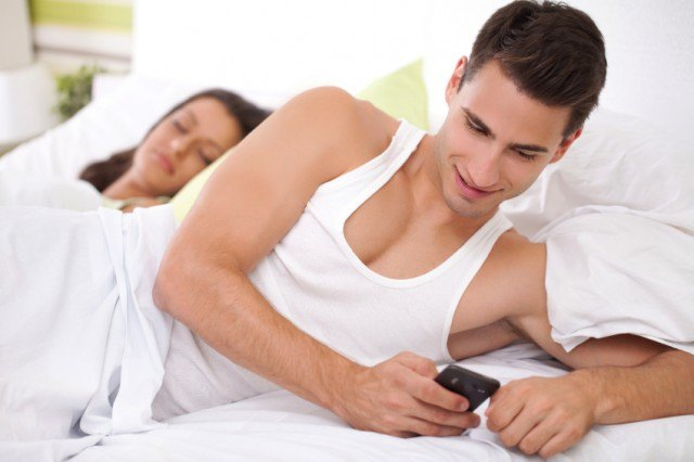 Smiling man secretly checking phone in bed